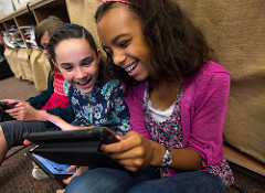 girls learning together on an iPad