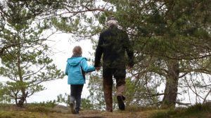 photo of parent and child walking through woods